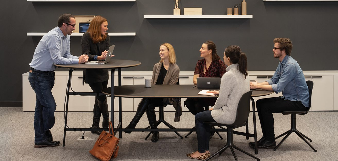 Image of colleagues chatting at multi-tiered desk
