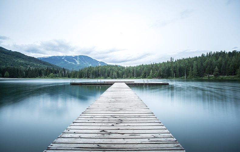 Image of a dock on a lake with trees and mountains in the distance