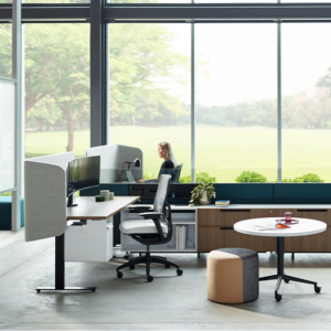 View of desk and workspaces with large windows and view of the outdoors
