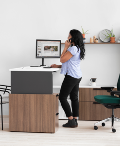 Image of woman standing at desk while talking on the phone