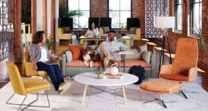 Image of lounge meeting area with colleagues chatting with dog on couch
