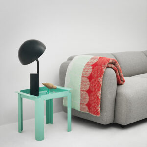 Sofa with accent blanket and teal side table