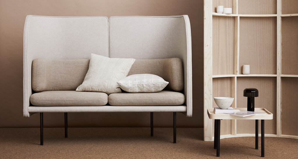 Neutral coloured seating area with high-back sofa and accent storage wall
