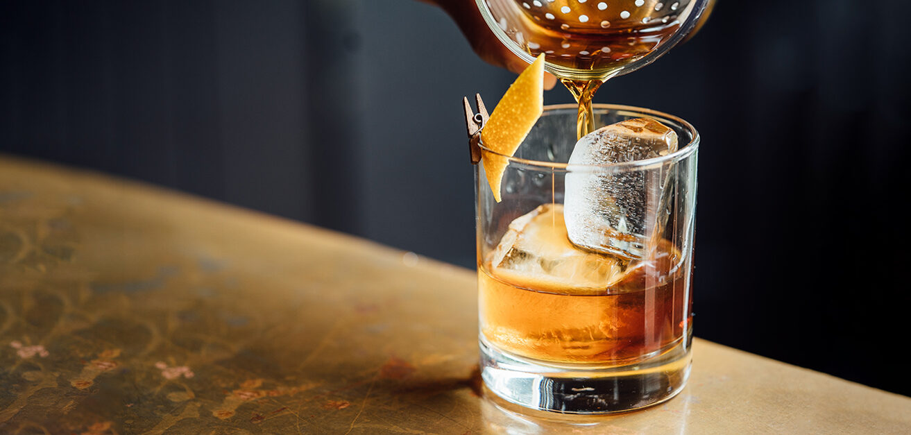 Close up of cocktail being poured into glass