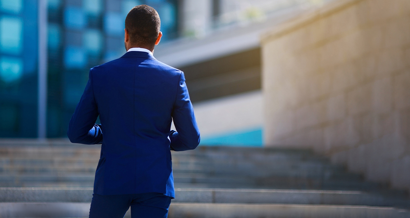 Man in blue suit facing office building stairs