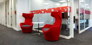 Two bright red accent chairs in front of meeting rooms