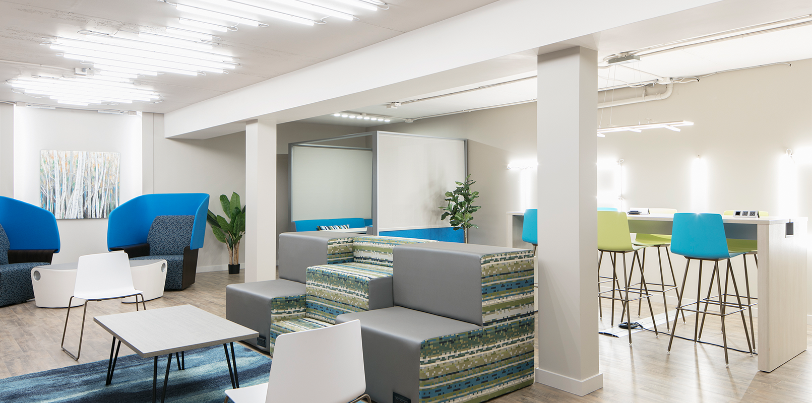Wide view of lounge and meeting space with accent chairs and neon lighting
